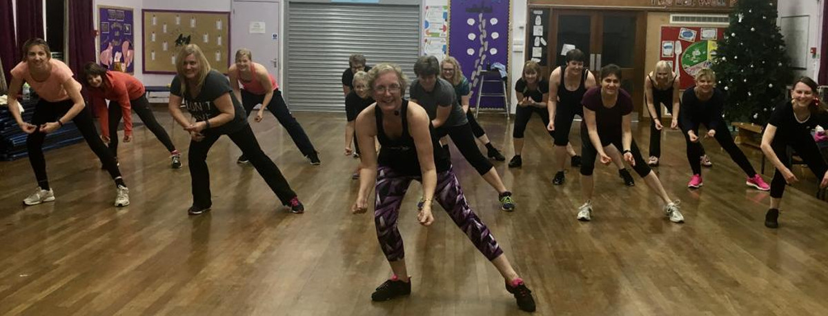 A group of ladies at a FitSteps dance class in a hall
