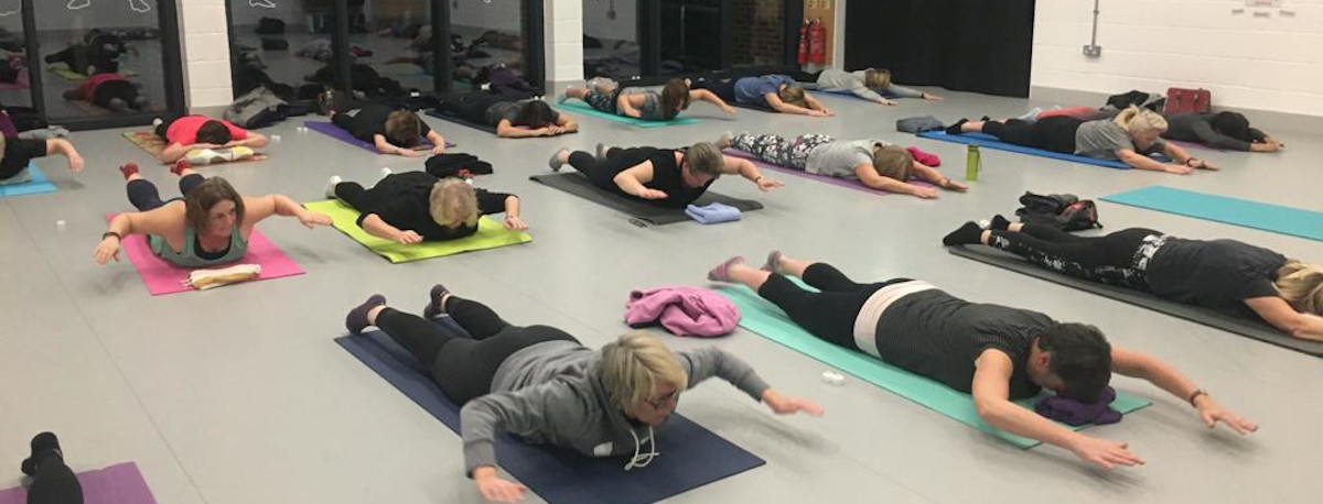 A group of people at a Pilates class in a hall